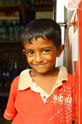 Chłopczyk mieszkający i zapewne pracujący w sklepiku na terenie starożytnej Anuradhapury. Zapraszam do sklepu angielskim Come In i rozbrajał uśmiechem.
