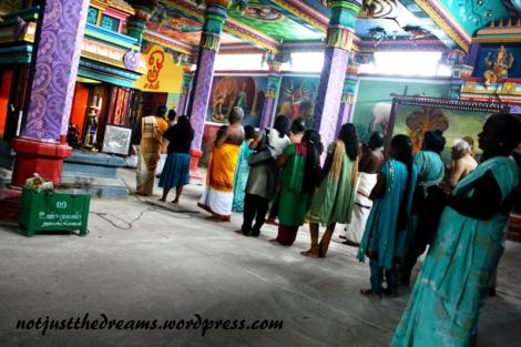 Wewnątrz grupa wiernych chodzi dookoła świątyni, zatrzymując się i modląc w kilku miejscach.