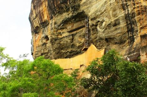 """Widoczny pomarańczowy """"mur"""" to ustrzana ściana. Nad nią widoczne są schody prowadzące do malowideł."""