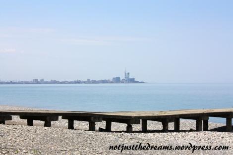 Plaża, mostek i Batumi na horyzoncie.