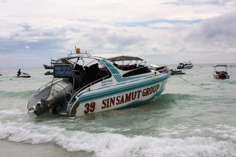 Przy brzegu pełno jest łodzi i skuterów wodnych.